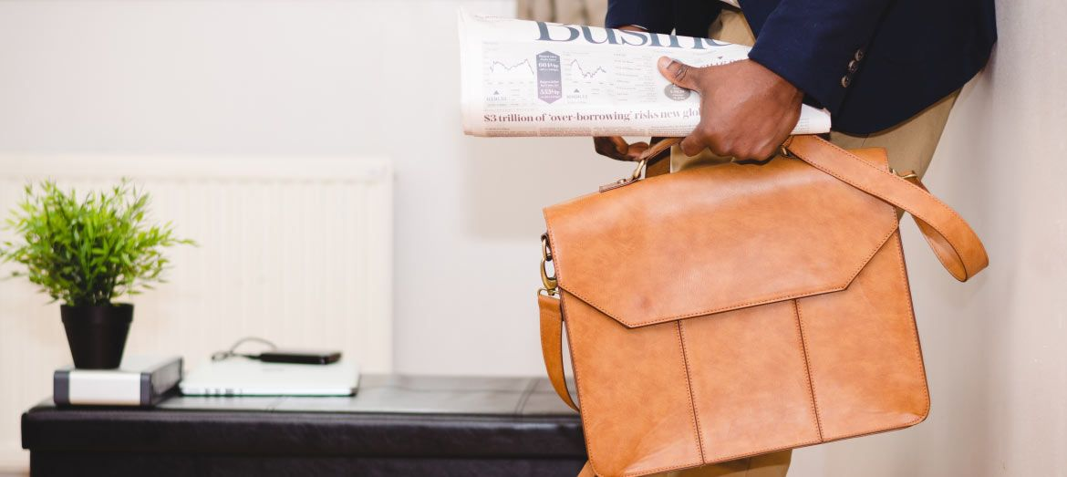 african-american male holding business section of newspaper and light brown briefcase