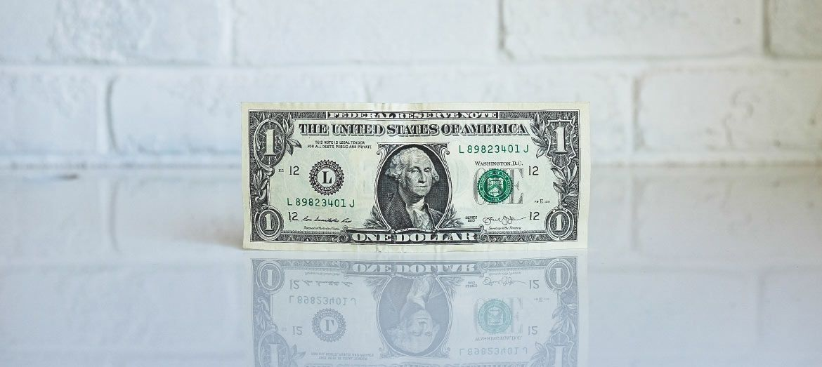a U.S. one dollar bill standing up straight with white background and white clear floor