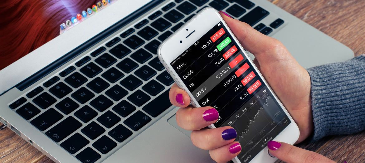 Woman with purple nail polish looking at stock market figures on mobile device with laptop in background